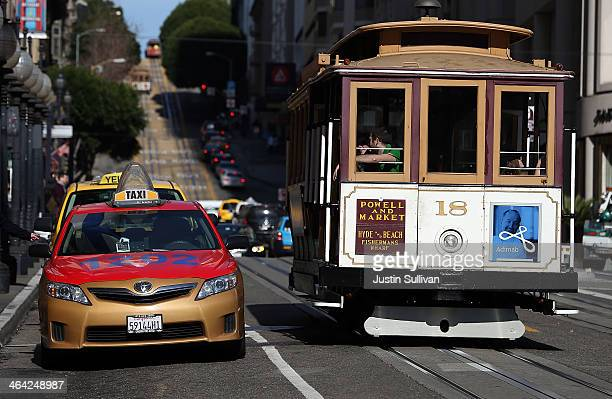 Cable Car passes a line of taxicabs as they wait for fares in front of the St Francis Hotel on January 21 2014 in San Francisco California As...