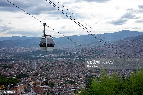 A cable car travels over the Santo Domingo neighborhood of Medellin Colombia on Thursday July 17 2014 Colombia's growth in the second quarter was...