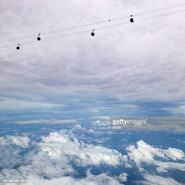 Cable cars against cloudy sky