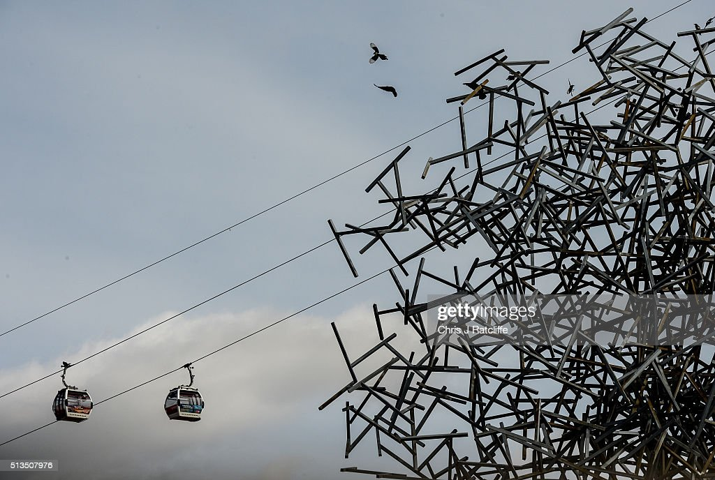 Cable cars run past the 'Quantum Cloud' sculpture by Antony Gormley on the Emirates Air Line as birds fly and settle on the sculpture over the river...