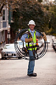 Cable installer carrying video cables on a street