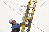 Cable lineman climbing a ladder in front of a satellite dish