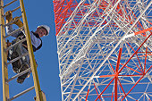 Cable lineman climbing down a ladder