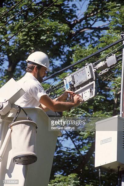 A cable technician installs television service near a utility pole 1980s