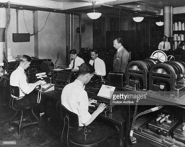 Cablegram operators work at desks while a supervisor watches at a Western Union office At left a man receives cables and at right a man sends cables...
