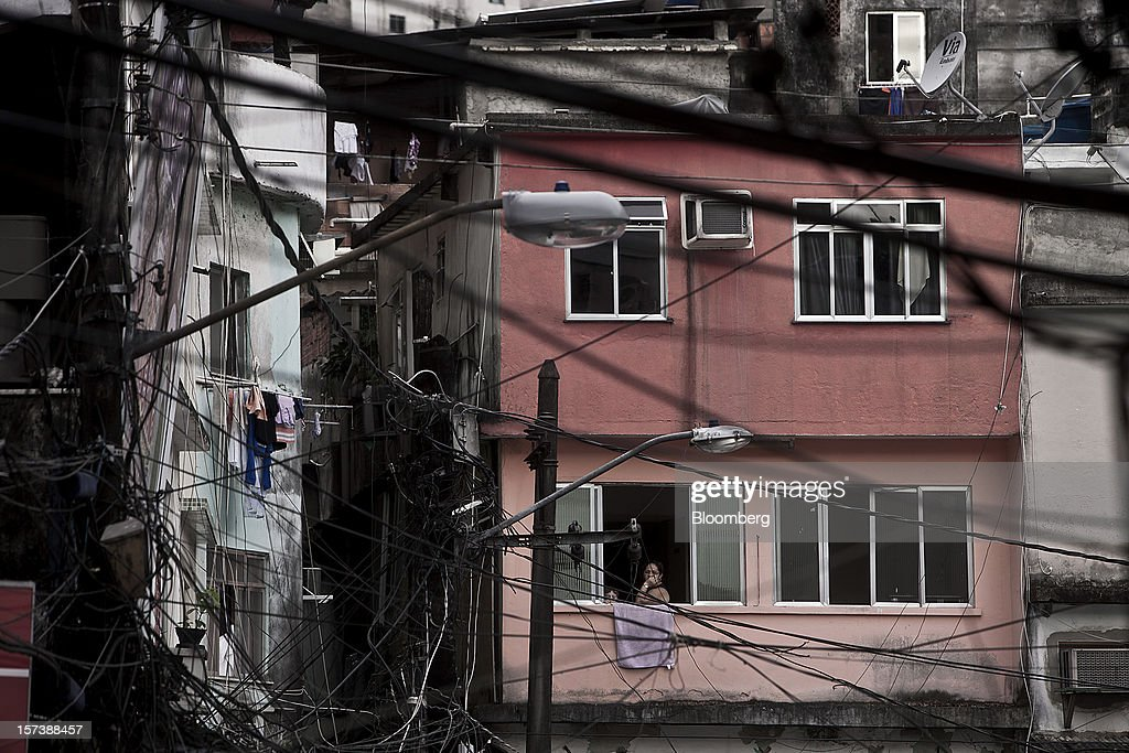 Cables and power lines hang from buildings and posts as a woman looks out of a window in the Rocinha slum of Rio de Janeiro, Brazil, on Wednesday, Nov. 28, 2012. About 56 percent of the 12 million people who live in slums like Rocinha were considered middle class in 2011, up from 29 percent in 2001, according to a study this year by Instituto Data Popular, a Sao Paulo-based research group. Photographer: Dado Galdieri/Bloomberg via Getty Images