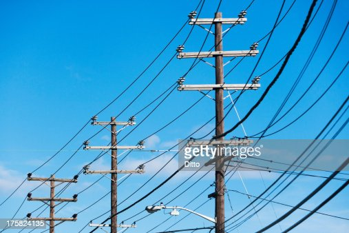Cables attached to telegraph pole against blue sky