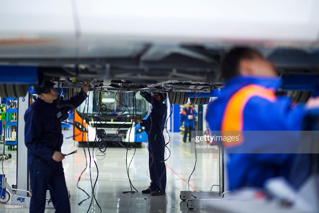 Cables hang from the underside of a bus as employees work on assembly at Volvo AB's bus manufacturing plant in Wroclaw, Poland, on Friday, Jan. 11, 2013. Volvo plans to end bus making in Saeffle by June 2013, and will consolidate the business in Europe to its main plant in Wroclaw, Poland, the Gothenburg, Sweden-based company said. Photographer: Bartek Sadowski/Bloomberg via Getty Images