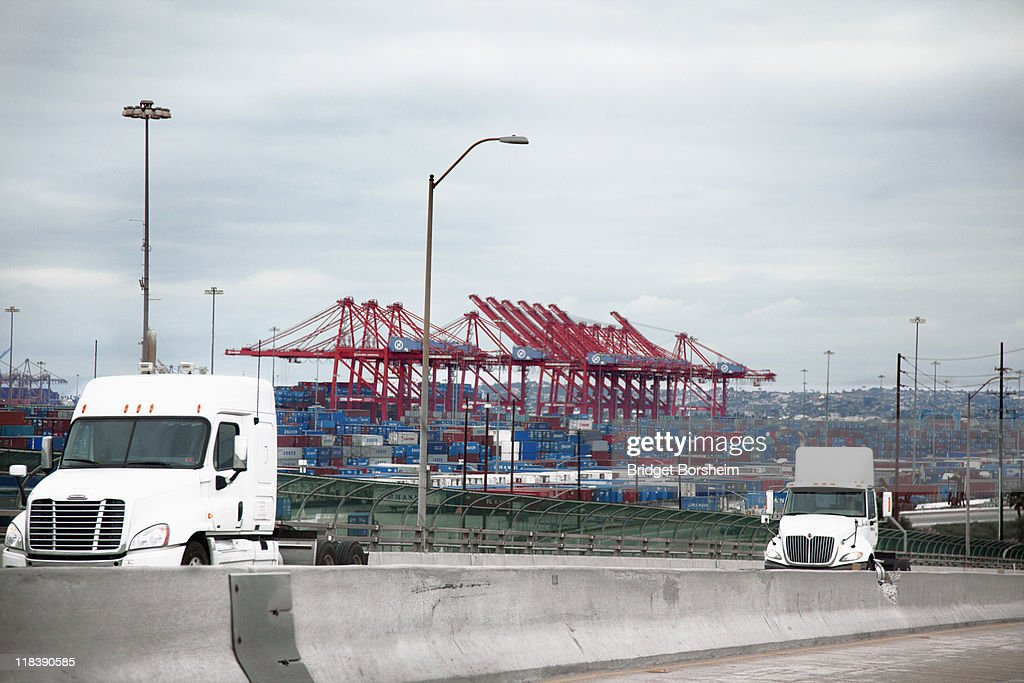 Cabs of empty Semi-Trucks in front of large port : Stock Photo