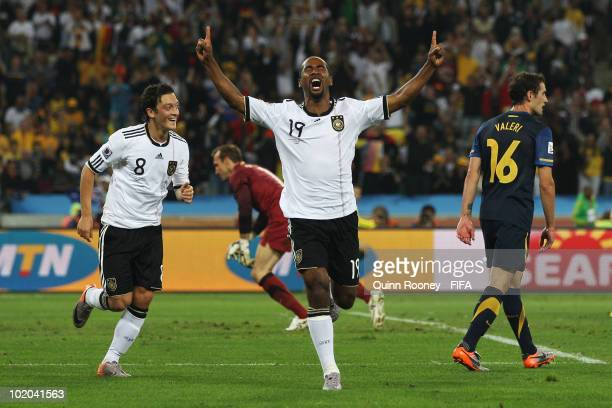 Cacau of Germany celebrates with team mate Mesut Oezil scoring his side's fourth goal while goalkeeper Mark Schwarzer and Carl Valeri of Australia...
