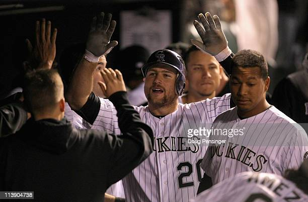 Cacther Chris Iannetta of the Colorado Rockies celebrates in the dugout after his solo homerun off of starting pitcher Chris Capuano of the New York...