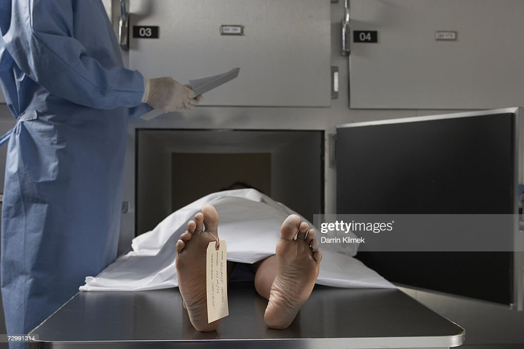 'Cadaver on autopsy table, label tied to toe, close-up' : Stock Photo