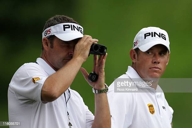 Caddie Billy Foster uses a range finder as his player Lee Westwood of England looks on during a practice round prior to the start of the 111th US...