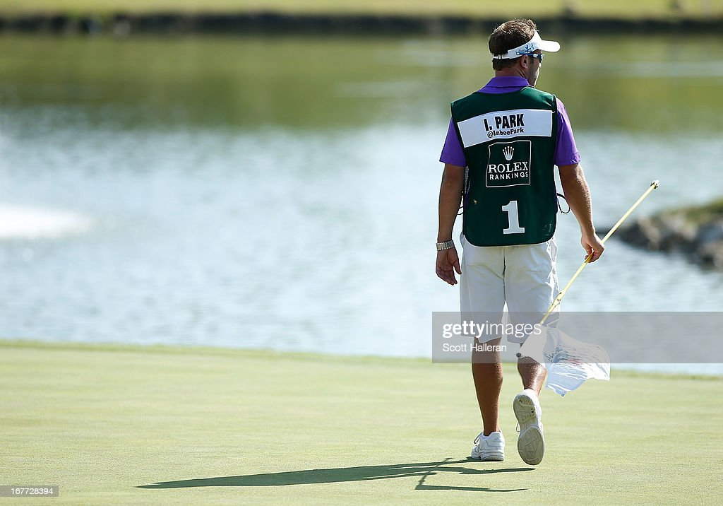 Caddie Brad Beecher walks across the 18th green during the final round of the 2013 North Texas LPGA Shootout at the Las Colinas Counrty Club on April 28, 2013 in Irving, Texas.