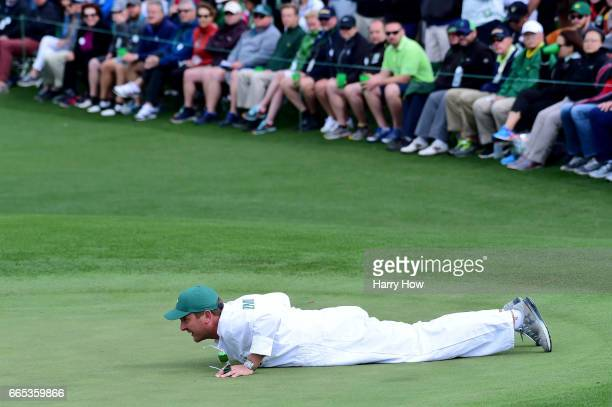 Caddie for Matthew Fitzpatrick of England Jamie Lane lines up a putt on the second green during the first round of the 2017 Masters Tournament at...