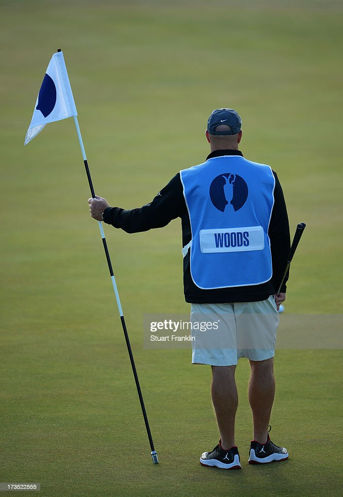 Caddie Joe LaCava holds the flag as Tiger Woods of the United States hits a shot ahead of the 142nd Open Championship at Muirfield on July 16, 2013 in Gullane, Scotland.