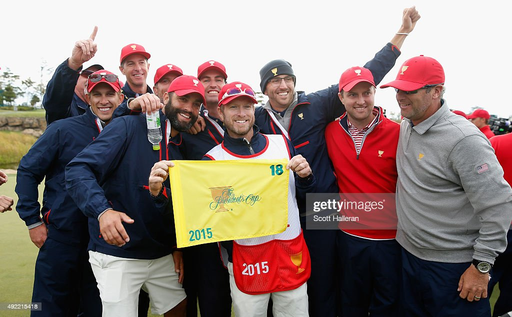 Caddie John Wood (C) of The United States Team poses with fellow caddies on the 18th green after their 15.5-14.5 win over the International Team during the Sunday singles matches at The Presidents Cup at Jack Nicklaus Golf Club Korea on October 11, 2015 in Songdo IBD, Incheon City, South Korea.