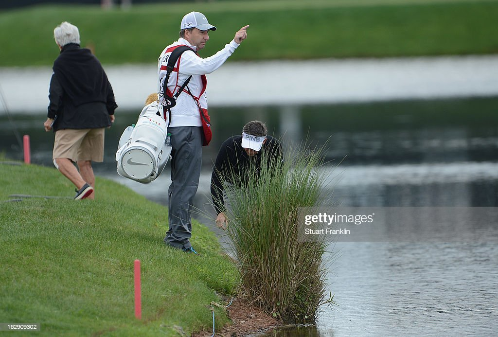 Caddie J.P Fitzgerald signals to World number one and defending champion, Rory McIlroy of Northern Ireland that his approach shot is in the water on the 16th hole where he took a triple bogey seven during the second round of the Honda Classic on March 1, 2013 in Palm Beach Gardens, Florida.