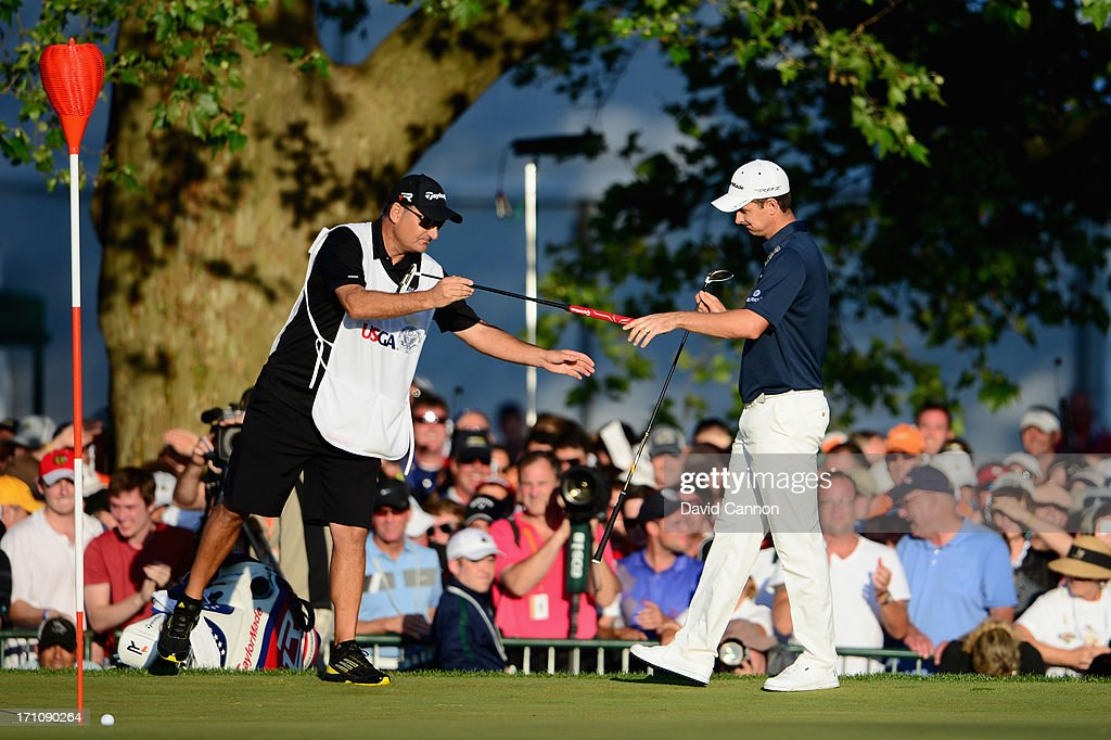 Caddie Mark Fulcher and Justin Rose of England exchange clubs on the 18th green during the final round of the 113th U.S. Open at Merion Golf Club on June 16, 2013 in Ardmore, Pennsylvania.