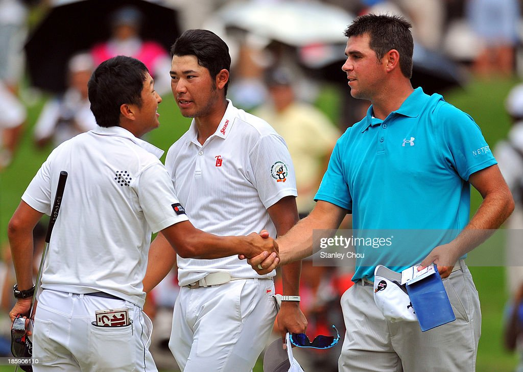 Caddie of Hideki Matsuyama of Japan shakes hands with Gary Woodland of USA while Hideki Matsuyama looks on after completion of play on the 18th hole during round three of the CIMB Classic at Kuala Lumpur Golf & Country Club on October 26, 2013 in Kuala Lumpur, Malaysia.