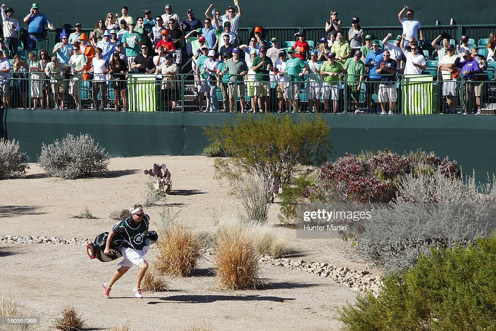 A caddie races to the green as fans cheer on the 16th hole during the third round of the Waste Management Phoenix Open at TPC Scottsdale on February 2, 2013 in Scottsdale, Arizona.