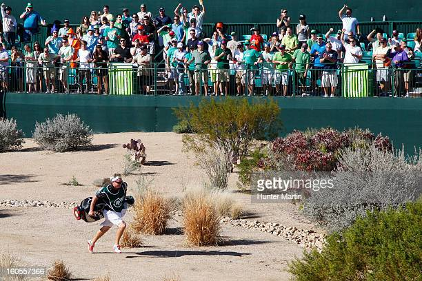 A caddie races to the green as fans cheer on the 16th hole during the third round of the Waste Management Phoenix Open at TPC Scottsdale on February...