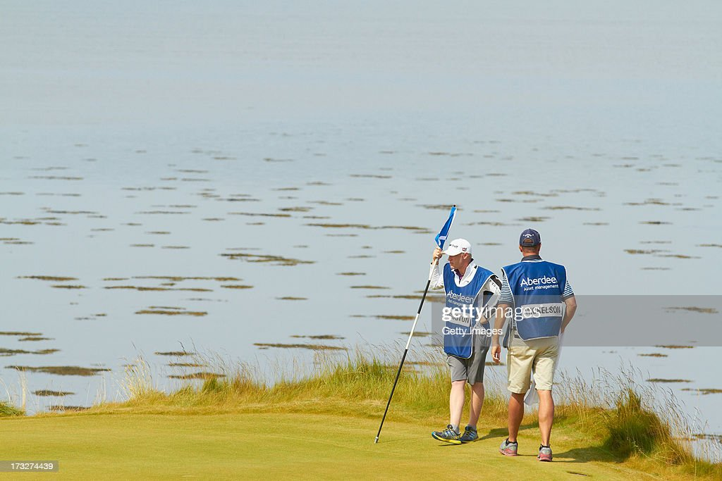 Caddies look on during the first round of the Aberdeen Asset Management Scottish Open at Castle Stuart Golf Links on July 11, 2013 in Inverness, Scotland.