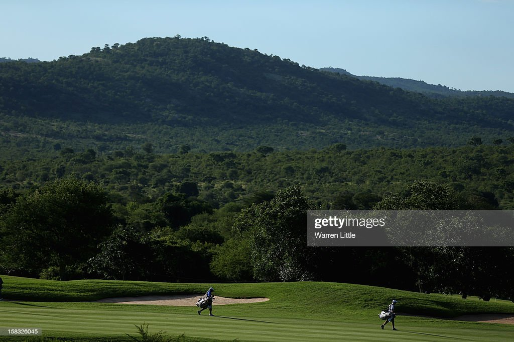 Caddies make their way down the 18th hole during the first round of the Alfred Dunhill Championship at Leopard Creek Country Golf Club on December 13, 2012 in Malelane, South Africa.