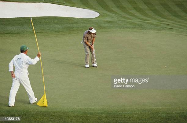Caddy Dave Musgrove looks on as Sandy Lyle of Great Britain holes out his putt on the final 18th hole to win the US Masters Golf Tournament on 10th...