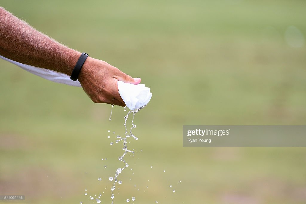 A caddy wets a towel during the second round of the World Golf Championships-Bridgestone Invitational at Firestone Country Club on July 1, 2016 in Akron, Ohio.