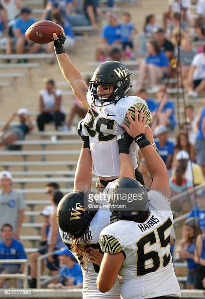 Cade Carney of the Wake Forest Demon Deacons celebrates with teammates after scoring the third of his three touchdowns against the Duke Blue Devils...