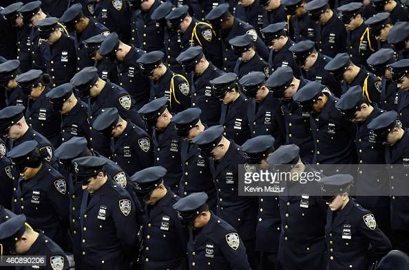 Cadets bow their heads during the New York Police Department graduation ceremony at Madison Square Garden on December 29 2014 in New York City New...