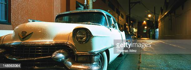 Cadillac (1952) parked in alley at night.