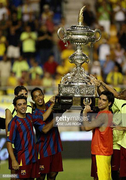 Barcelonas players show the trophy after winning the Carranza trophy against Cadiz CF at Ramon de Carranza Stadium in Cadiz 06 August 2005 AFP PHOTO/...