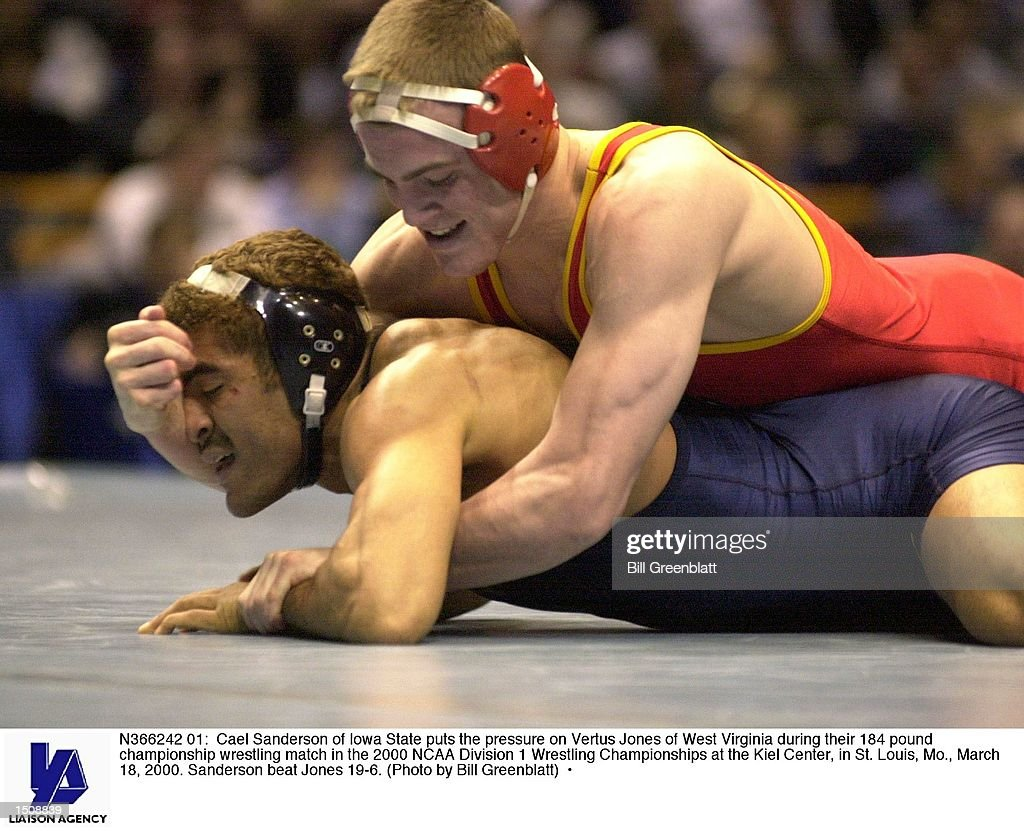 Cael Sanderson of Iowa State puts the pressure on Vertus Jones of West Virginia during their 184 pound championship wrestling match in the 2000 NCAA...