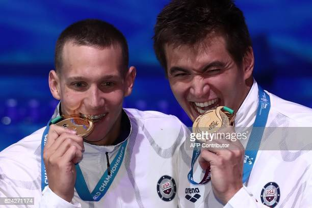 US Caeleb Remel Dressel and US Nathan Adrian celebrate on the podium after the mixed 4x100m freestyle final during the swimming competition at the...