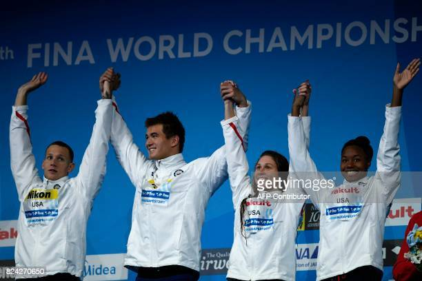 US Caeleb Remel Dressel US Nathan Adrian US Mallory Comerford and US Simone Manuel celebrate on the podium after the mixed 4x100m freestyle final...