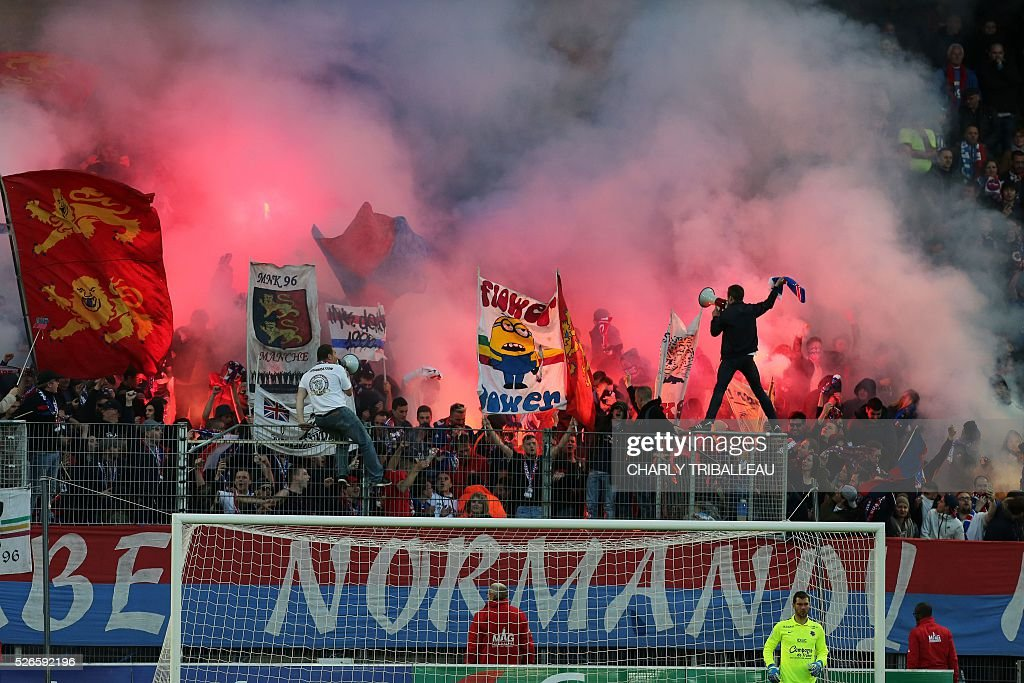 Caen supporters of the Malherbe Normandy Kop - MNK burn flares and waves flags as they celebrate their 20th anniversary during the French L1 football match between Caen (SMC) and Bastia (SCB) on April 30, 2016, at the Michel d'Ornano Stadium in Caen, northwestern France.