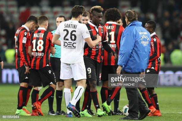 Caen's Croatian forward Ivan Santini and Nice's Italian forward Mario Balotelli react after the French L1 football match Nice vs Caen on March 10...