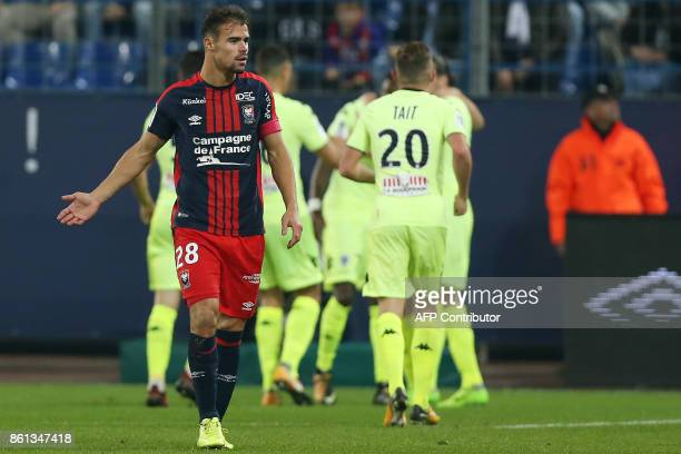 Caen's French defender Damien Da Silva reacts while Angers' players celebrate a goal during the French L1 football match between Caen and Angers on...