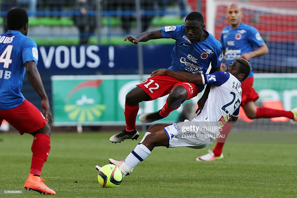 Caen's French defender Dennis Appiah (2nd R) falls with Bastia's Guinean forward Francois Kamano (R) during the French L1 football match between Caen (SMC) and Bastia (SCB) on April 30, 2016, at the Michel d'Ornano Stadium in Caen, northwestern France.