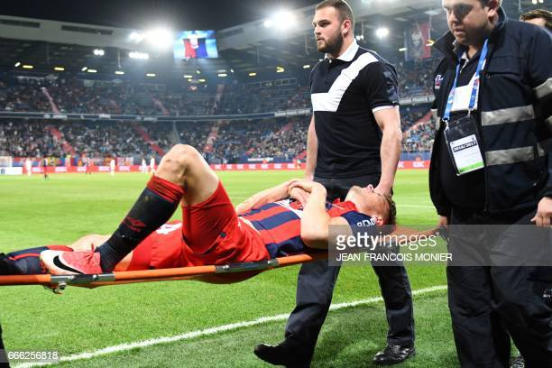 Caen's French defender Frederic GuiLbert lies on a stretcher as he is brought off the pitch after being injured during the French L1 football match...