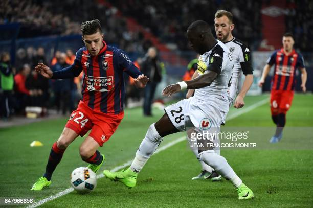 Caen's French defender Frederic Guilbert vies for the ball with Angers' Senegalese defender Issa Cissokho during the French L1 football match between...