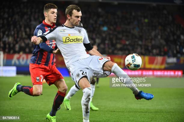 Caen's French defender Frederic Guilbert vies for the ball with Angers' French defender Romain Thomas during the French L1 football match between...