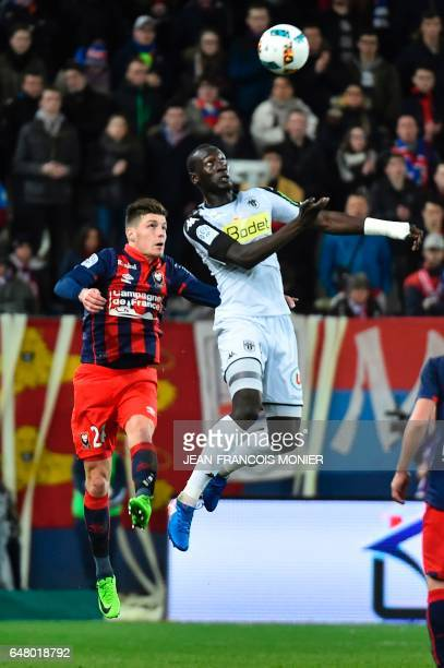 Caen's French defender Frederic Guilbert vies for the ball with Angers' French forward Famara Diedhiou during the French L1 football match between...
