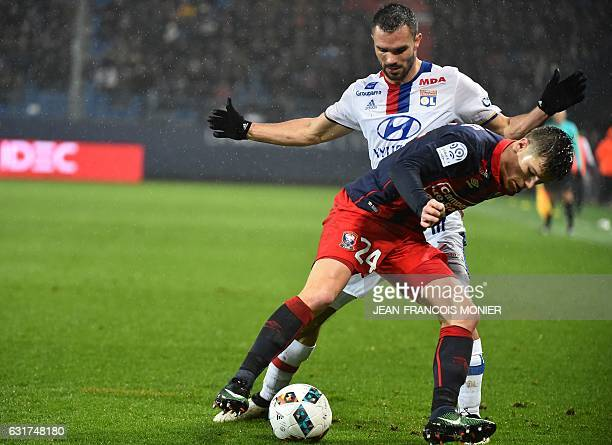 Caen's French defender Frederic Guilbert vies for the ball with Lyon's French defender Jeremy Morel during the French L1 football match between Caen...