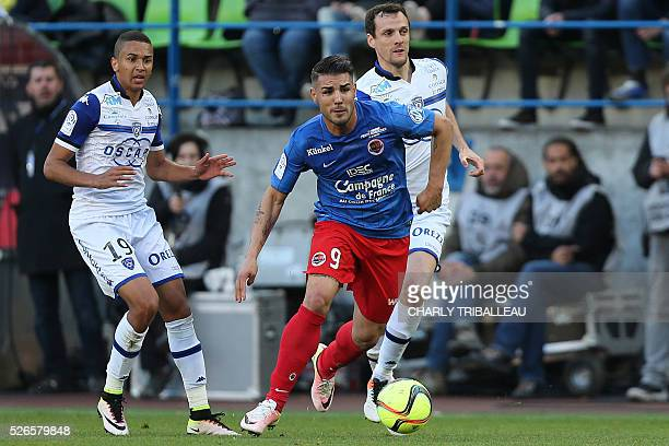 Caen's French forward Andy Delort vies for the ball with Bastia's French midfielder Axel Ngando and Bastia's French defender Sebastien Squillaci...