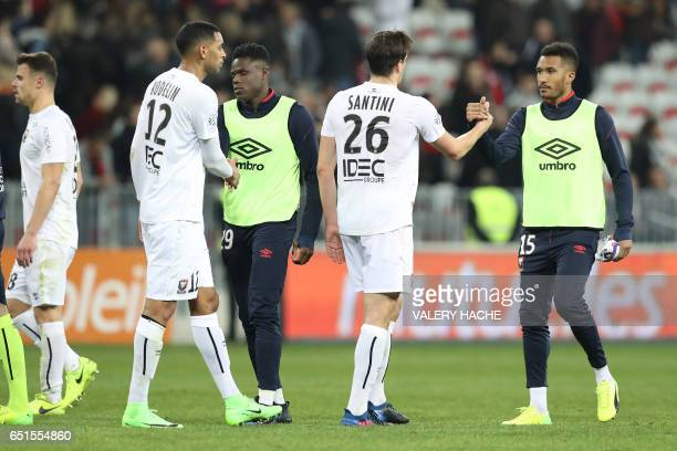 Caen's French forward Sylvio Ronny Rodelin and Caen's Croatian forward Ivan Santini shake hands with Nice's Brazilian defender Dalbert Henrique and...