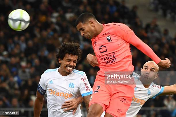 Caen's French forward Sylvio Ronny Rodelin heads the ball as he vies with Olympique de Marseille's Tunisien defender Aymen Abdennour during the...