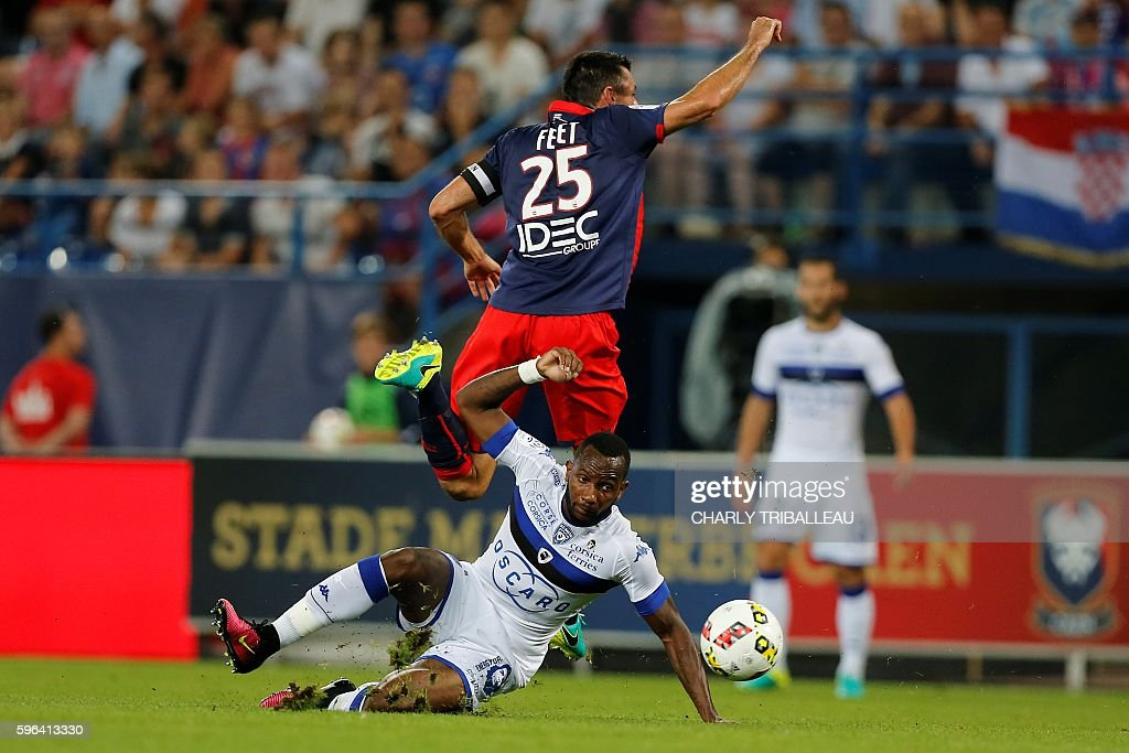 Caen's French midfielder Julien Feret jumps above with Bastia's French midfielder Lenny Nangis during the French L1 football match between Caen and...